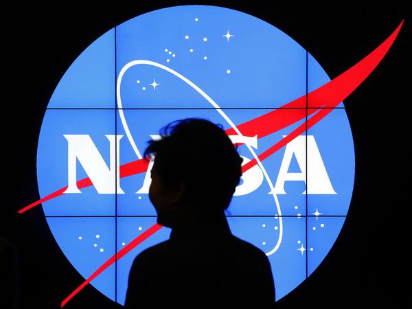South Korean President Park Geun-hye walks past a NASA logo during a tour at the agency's Goddard Space Flight Center in Greenbelt, Md.