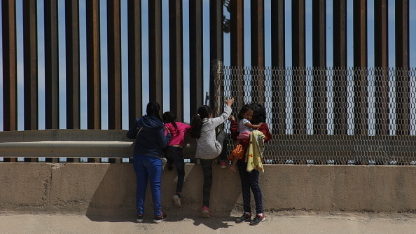A mother and her three daughters at the border crossing dividing Juárez, Mexico, and El-Paso, Texas. The family traveled from Guatemala to reach the U.S.