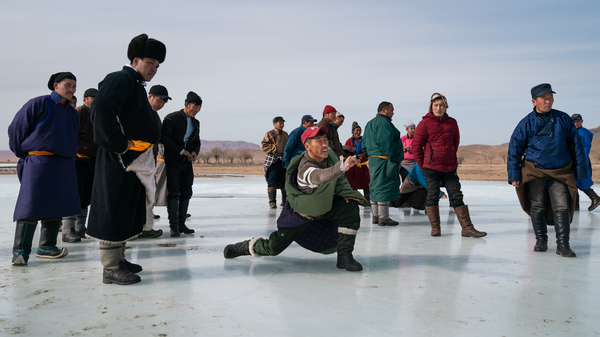 A group of Mongolian herdsmen gathers to play musun shagai (ice shooting) on the Tamir river in early March.