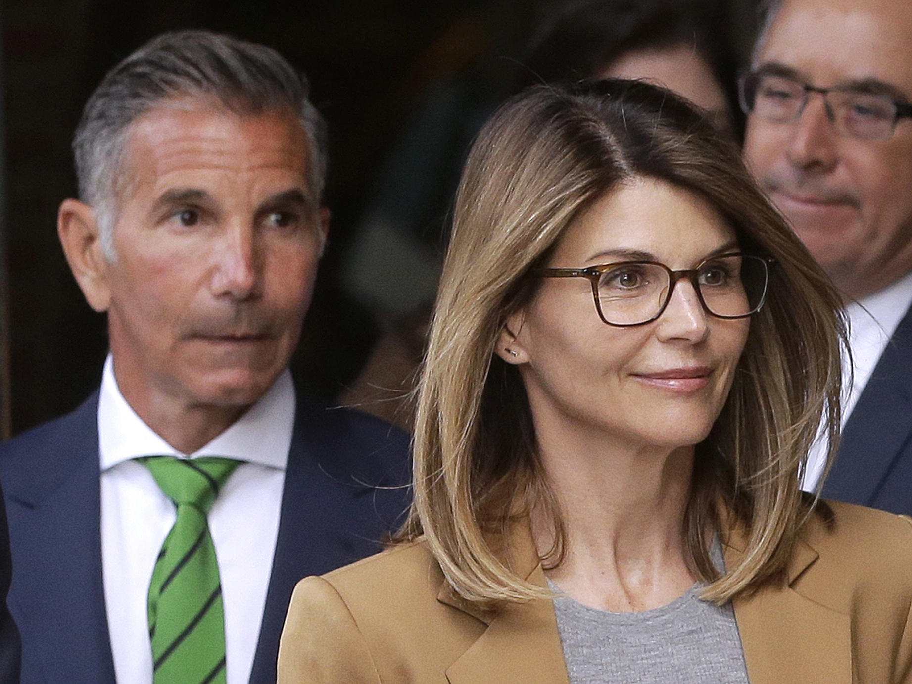 Actress Lori Loughlin and her husband, clothing designer Mossimo Giannulli (left), announced on Monday that they would plead not guilty to charges in the Justice Department's college admissions case. Here, they leave federal court in Boston earlier this month.