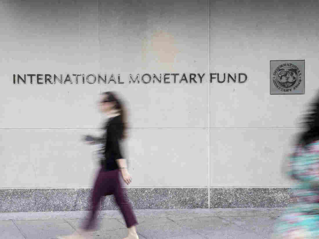 Pedestrians walk past the International Monetary Fund (IMF) headquarters in Washington, D.C.
