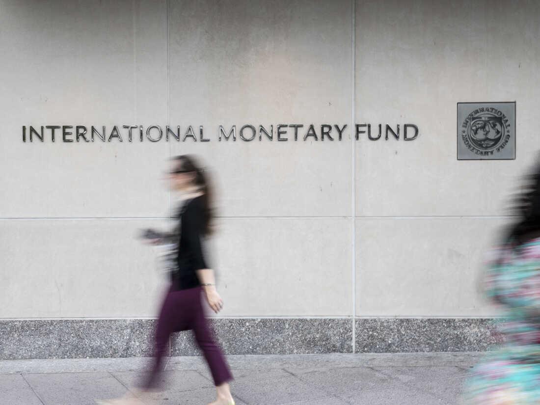 Pedestrians walk past the International Monetary Fund (IMF) headquarters in Washington, D.C.
