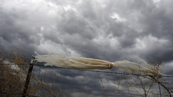 A plastic bag caught on a fence blows in the wind. Microplastic is formed from larger pieces of plastic that have broken down.