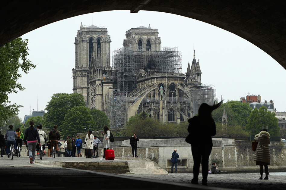 People look up at the damage caused to Notre Dame Cathedral on Tuesday in Paris. A fire broke out on Monday afternoon and quickly spread across the building, causing the famous spire to collapse. (Dan Kitwood/Getty Images)