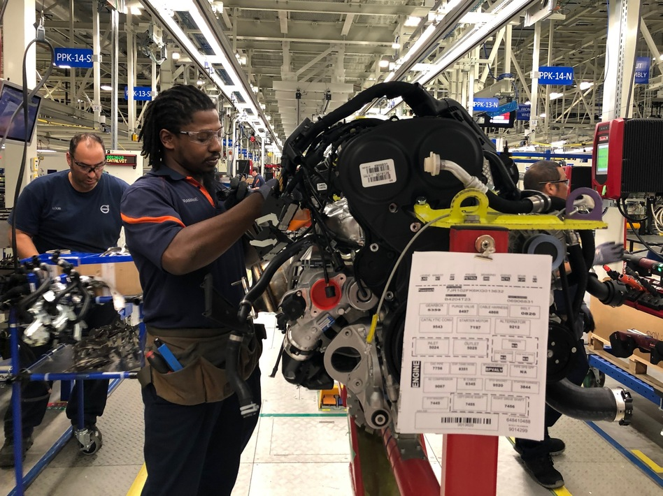 Tremaine Smalls (center) attaches parts to an engine at Volvo's plant in Ridgeville, S.C. The automaker has shifted its exports to Europe as the result of the U.S. trade war with China. (Camila Domonoske/NPR)