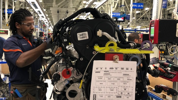 Tremaine Smalls (center) attaches parts to an engine at Volvo