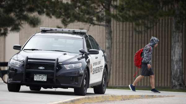 A student leaves Columbine High School late Tuesday in Littleton, Colo. Authorities say they are looking for a woman they say presented a credible threat ahead of the 20th anniversary of the mass shooting there.