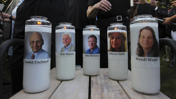 The photos of five people slain in the Capital Gazette newsroom adorn candles at a vigil in June. The attack was mentioned in the analysis of Reporters Without Borders' annual World Press Freedom Index.