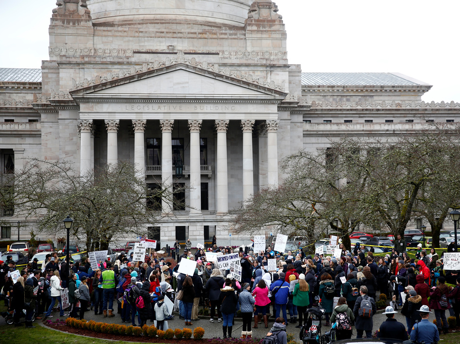 The Washington state Senate passed a bill on Wednesday that would remove the personal belief exemption from the required vaccinations for measles, mumps and rubella. Here, people protest the related house bill outside Washington's Legislative Building in Olympia in February. (Lindsey Wasson/Reuters)