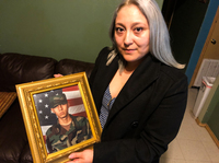 Edgar Baltazar Garcia's wife, Jennifer Garcia, holds a photo of her husband from when he was deployed at Balad Air Base in Iraq as a turret gunner in a Humvee. He now faces deportation to Mexico over a felony conviction.