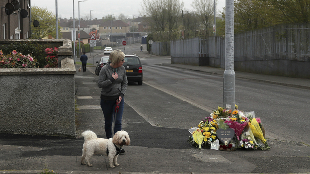 A woman stops to pay her respects at the scene on Saturday in Londonderry, Northern Ireland, where 29-year-old journalist Lyra McKee was fatally shot. (Brian Lawless/AP)