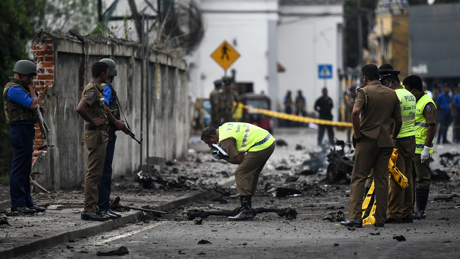Sri Lankan security personnel inspect the debris of a van after it exploded on Monday near St. Anthony's Shrine in Colombo. More than 300 people died and more than 500 were wounded after Sunday's attacks on churches and hotels. (Jewel Samad/AFP/Getty Images)