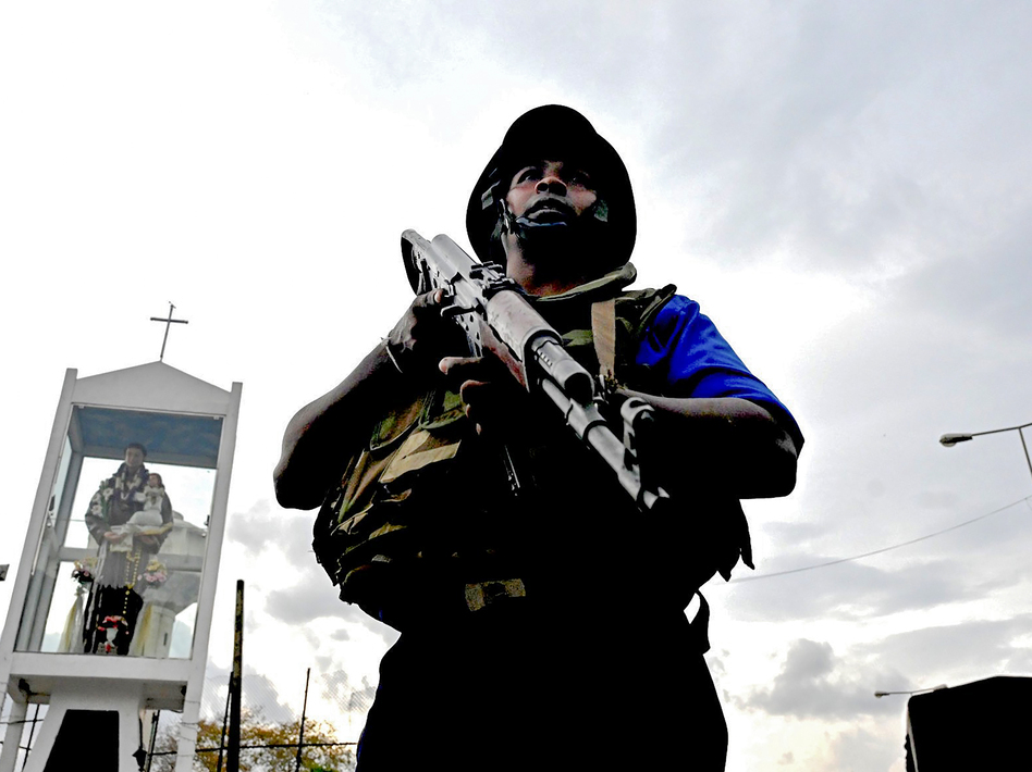 A Sri Lankan soldier stands guard near the site of a car explosion after police tried to defuse a bomb near St. Anthony's Shrine in Colombo on Monday, the day after a series of bomb blasts targeting churches and luxury hotels in Sri Lanka. (Jewel Samad/AFP/Getty Images)