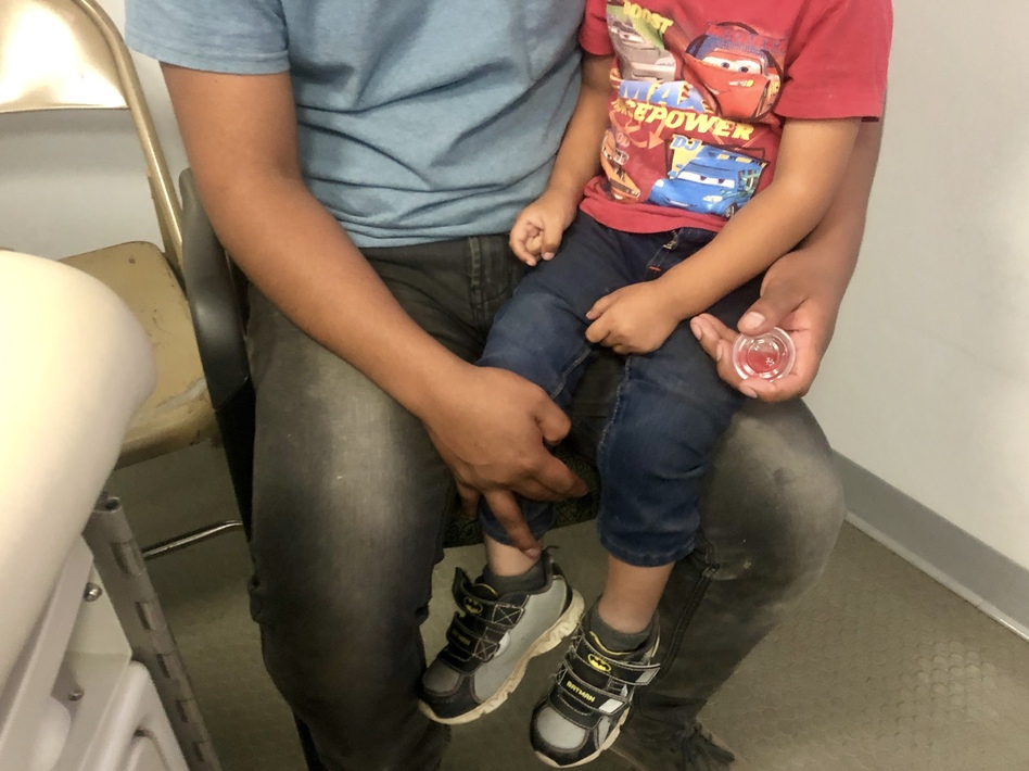 Sergio, a Guatemalan migrant, recently visited a mobile medical van with his 2-year-old son, Dylan. Sergio thinks his son became sick in a holding facility, where they spent two days. (Mallory Falk/KRWG)