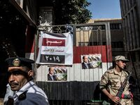 An Egyptian soldier and a policeman stand guard at a Cairo polling station on Monday, the third day of a referendum on constitutional amendments.