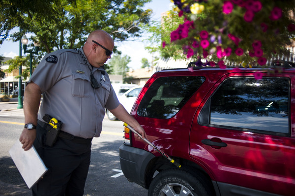 A traffic enforcement officer chalks tires in Arvada, Colo., in 2014. Physically marking a tire without a warrant is a violation of the Fourth Amendment, a federal appeals court ruled.