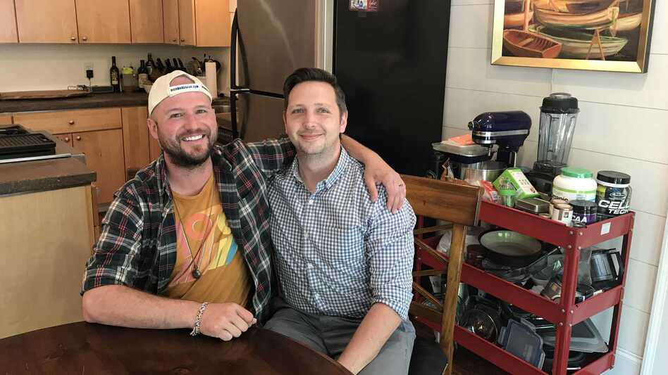 Greg McDonald Jr. (left) sits with his fiancé Jon Jost. McDonald's parents considered sending him to counseling when they were concerned he was gay. Now they support a ban on conversion therapy. (Leila Fadel/NPR)