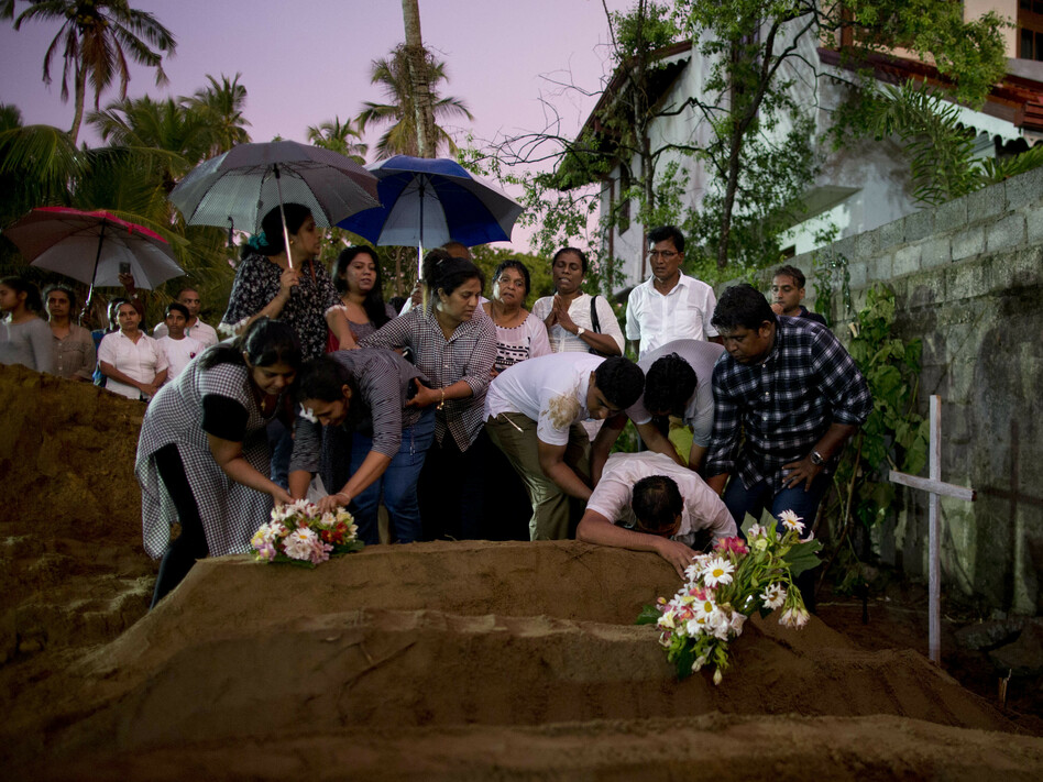 Relatives place flowers after the burial of three family members who died in an Easter Sunday bomb blast at St. Sebastian Church in Negombo, Sri Lanka, on Monday. (Gemunu Amarasinghe/AP)