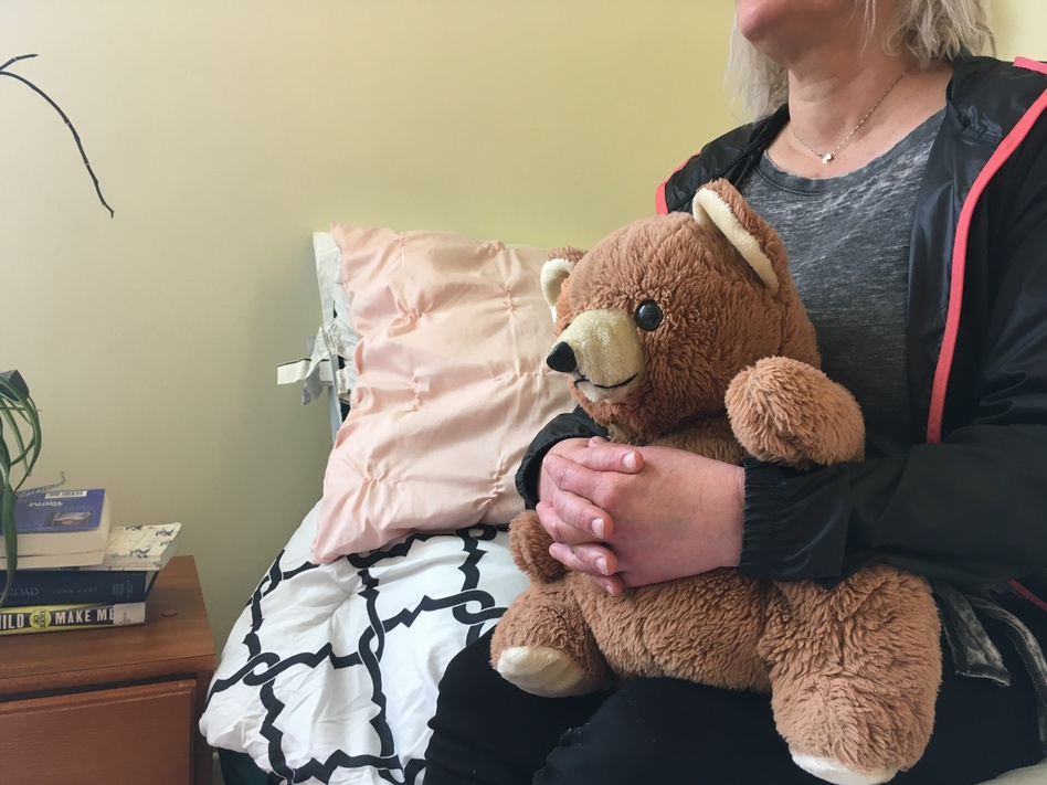 "Kim has been living at the Epiphany Center, a treatment facility in San Francisco for women struggling with addiction, for the past six months. She says her teddy bear is her only material possession left from her past: ""Because everything I had, I've lost over and over again."" (April Dembosky/KQED)"
