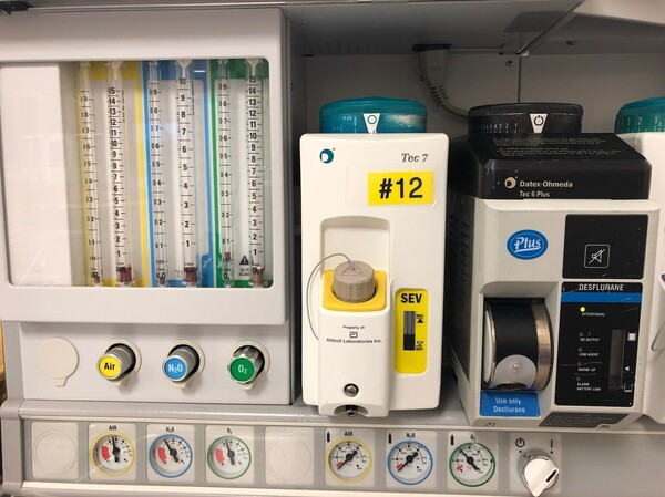 An anesthesia cart contains canisters for desflurane (right, with blue decals) and sevoflurane (center, with yellow decals). Both anesthetics are greenhouse gases, but desflurane's impact on global warming is 20 times as bad as sevoflurane's, Chesebro learned.