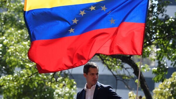 Venezuelan opposition leader and self-proclaimed acting president Juan Guaido is pictured under a national flag during a gathering with supporters after members of the Bolivarian National Guard joined his campaign to oust President Nicolas Maduro, in Caracas on April 30.