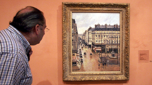 "This 2005 photo shows a visitor viewing the Impressionist painting called ""Rue St.-Honore, Apres-Midi, Effet de Pluie"" painted in 1897 by Camille Pissarro, on display in the Thyssen-Bornemisza Museum in Madrid."