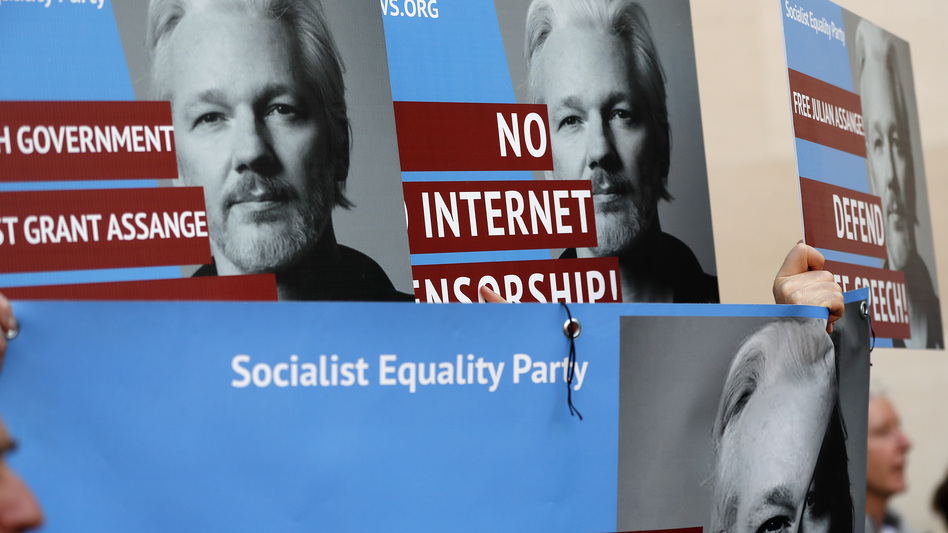 Protesters carry posters depicting Julian Assange outside Westminster Magistrates Court in London on Thursday where the WikiLeaks founder appeared by video link from prison for an extradition hearing. (Frank Augstein/AP)