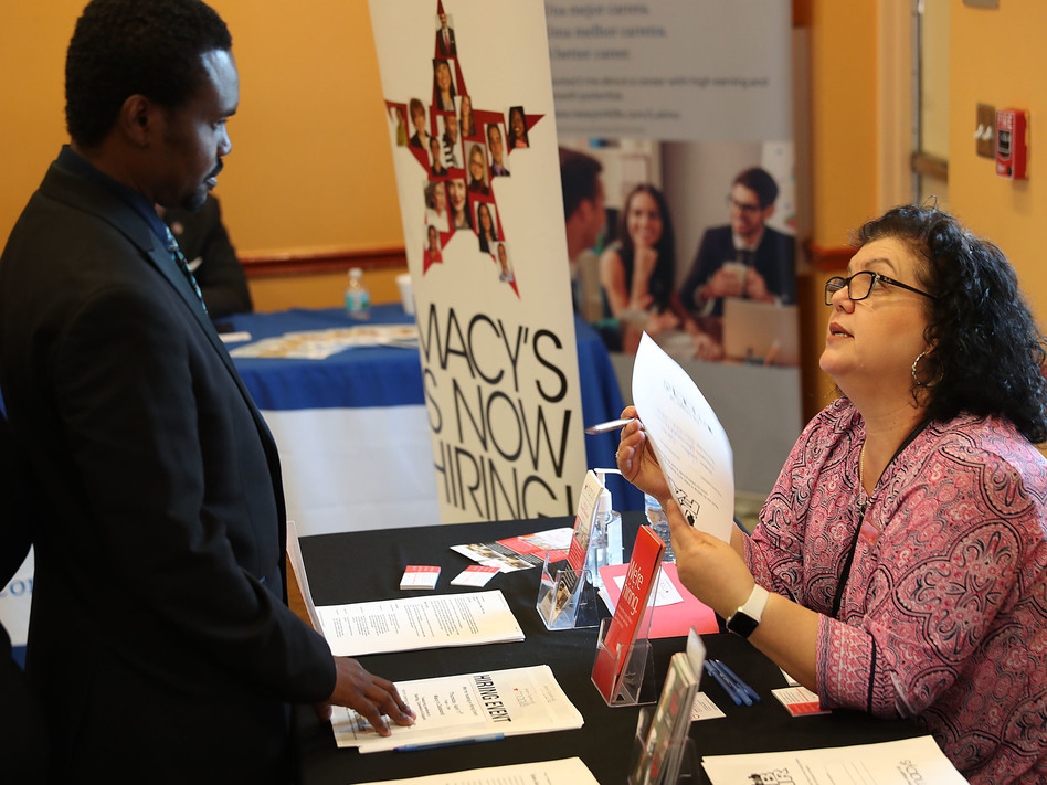 Betty Fernandez of Macy's department store speaks with a potential applicant about job openings during a job fair in Miami on April 5. Employers added far more jobs than expected in April — another sign the U.S. economy is chugging along as the expansion nears the 10-year mark. (Joe Raedle/Getty Images)
