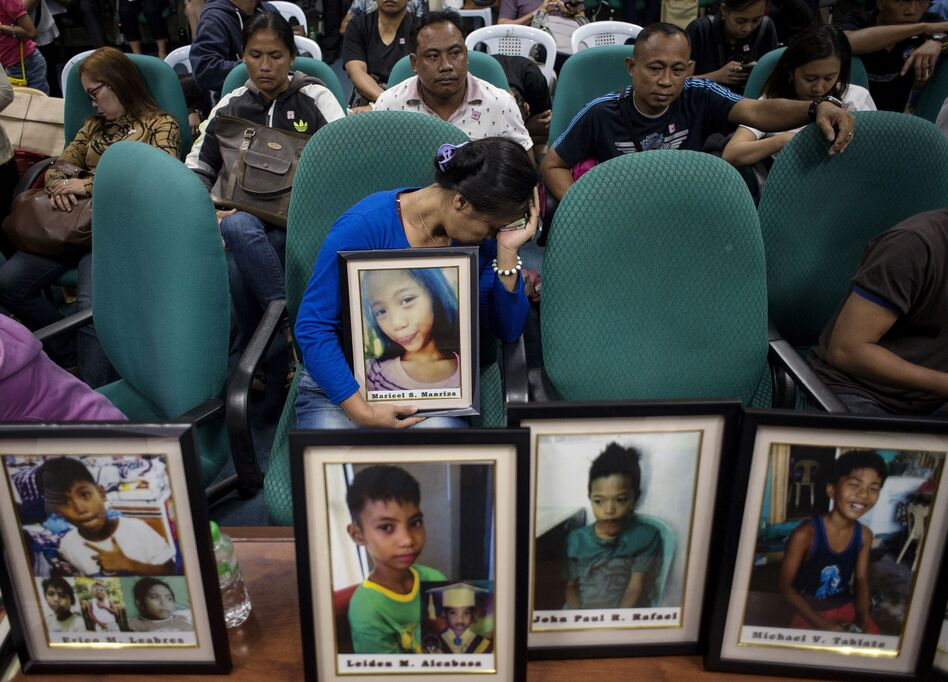 At a Feb. 21, 2018, Philippine Senate hearing in Manila on deaths linked to the dengue vaccine, families brought photos of children who had been vaccinated. (Noel Celis /AFP/Getty Images)