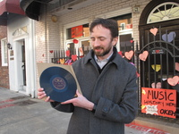 """Kyle Kessler holds a pressing of Fiddlin' John Carson's """"The Little Old Log Cabin in the Lane,"""" which was recorded at 152 Nassau Street in Atlanta."""