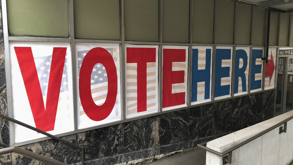 "A ""vote here"" sign marks the entrance to an early voting station in downtown Minneapolis in 2018. (Steve Karnowski/AP)"