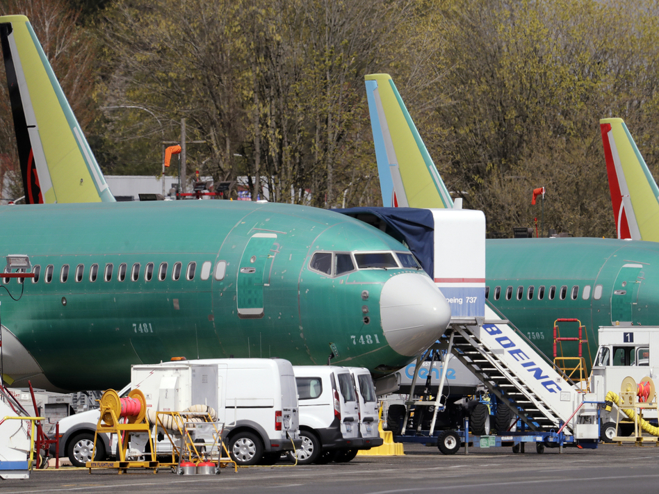 Boeing said on Sunday that it was aware of problems with a key safety indicator in 2017, but it didn't inform airlines or the FAA until after the Lion Air crash a year later. Here, 737 Max jets built for American Airlines (left) and Air Canada are parked at the airport adjacent to a Boeing production facility in Renton, Wash., in April. (Elaine Thompson/AP)