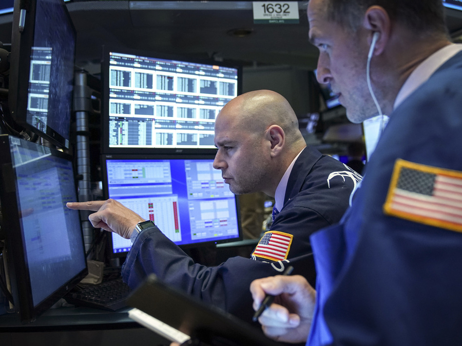 Traders and financial professionals work on the floor of the New York Stock Exchange on Monday. U.S. stock markets fell sharply at the open but crept higher as the day wore on after President Trump threatened to raise tariffs on imports from China. (Drew Angerer/Getty Images)