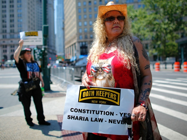A Trump supporter holds up a sign during an anti-Sharia law rally organized by ACT for America. A new report finds that mainstream philanthropies are unknowingly funneling donations to anti-Muslim groups such as ACT for America.