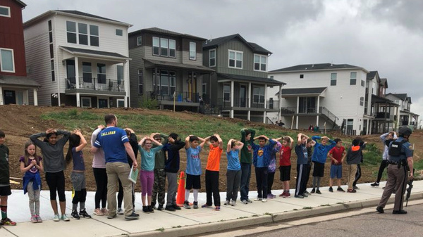 Schoolchildren stand in a line near the STEM School in Highlands Ranch during a shooting at the Colorado school, in an image obtained by Reuters via social media.