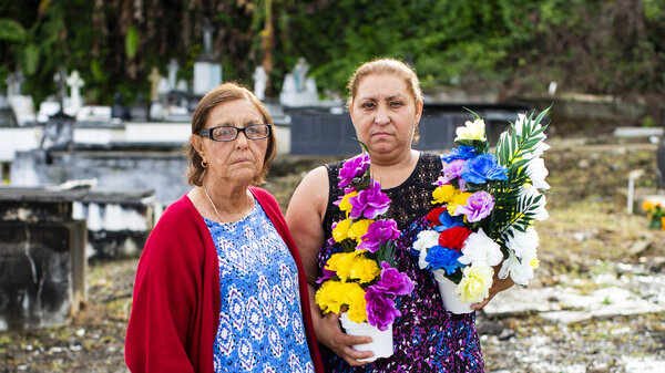 Eligia González, 84, (left) and her daughter, Carmen Román, 54, brought flowers to the Lares Municipal Cemetery. Román felt she had been deceived, after she realized her grandmother's grave was inaccessible.
