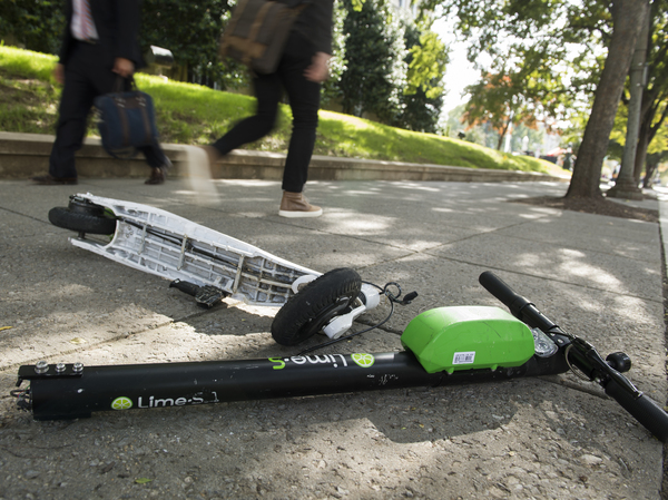 A broken Lime electric scooter lays on a sidewalk in Washington, D.C.