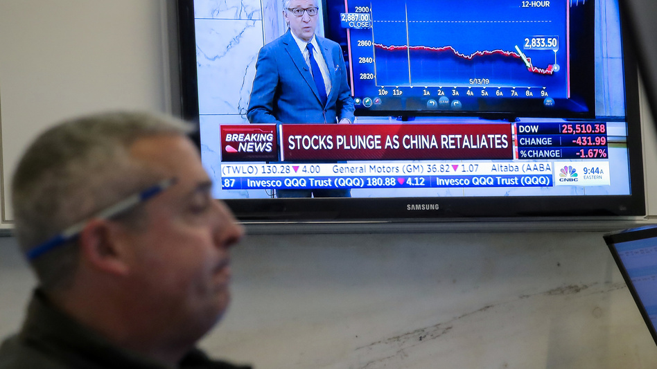 U.S. stocks fell sharply Monday after China retaliated for President Trump's latest round of tariffs. Here, a trader works on the floor at the New York Stock Exchange as a TV shows the state of the market. (Brendan McDermid/Reuters)