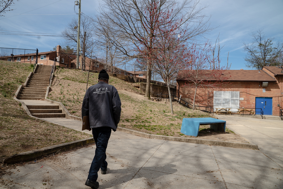 An employee of the District of Columbia Housing Authority walks on the grounds of a public housing complex called Richardson Dwellings in Northeast Washington, D.C. The Trump administration wants to eliminate the federal fund now used to repair public housing in favor of attracting more private investment to repair and replace it. (Amr Alfiky/NPR)