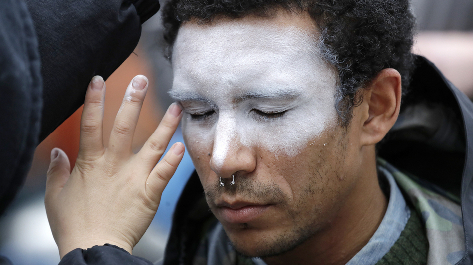 In this Oct. 31 photo, a man has his face painted to represent efforts to defeat facial recognition. It was during a protest at Amazon headquarters over the company's facial recognition system. (Elaine Thompson/AP)