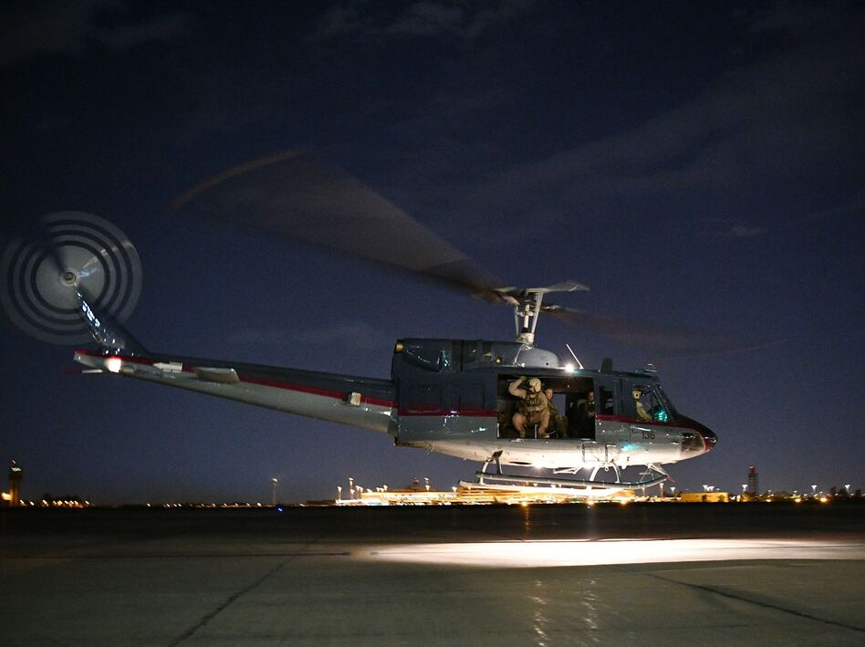 """The State Department ordered """"non-emergency"""" U.S. government employees out of Iraq on Wednesday. A helicopter carrying U.S. Secretary of State Mike Pompeo is seen taking off from Baghdad International Airport last week. (Mandel Ngan/AFP/Getty Images)"""
