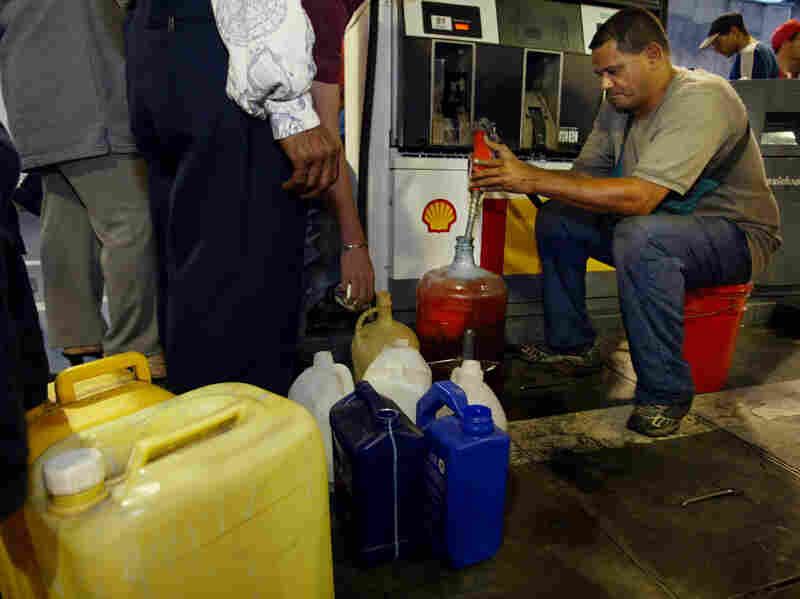 People fill containers with gasoline after waiting for hours at a gas station in Caracas on December 21, 2002. This was the twentieth day of a general strike protesting the rule of President Hugo Chavez and Venezuela's struggling oil industry.