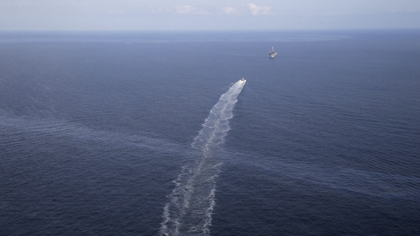 The wake of a supply vessel heading toward a working platform crosses over an oil sheen drifting from the site of the former Taylor Energy oil rig in the Gulf of Mexico in 2015. The Coast Guard says it has contained the oil spill.