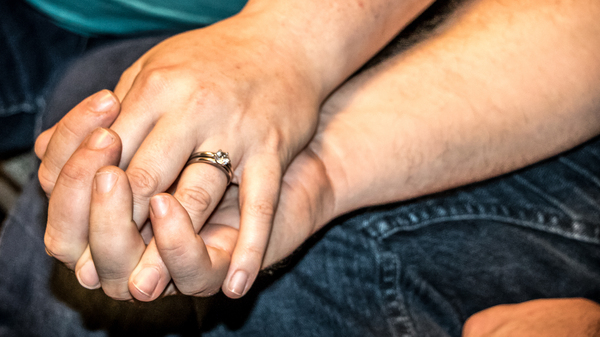 Greg and Judy hold hands at their home in Guthrie, Okla. The couple can't find integrated mental health and opioid addiction treatment for Greg in their area.
