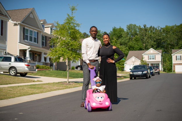 Sam Smith, Brittany Smith and their daughter Erelah outside their Charlotte home. The Smiths moved to Charlotte looking for change and opportunity. They are part of an influx of African Americans to Mecklenburg County, where the African American population has ballooned by 64% since 2000. (Swikar Patel for NPR)