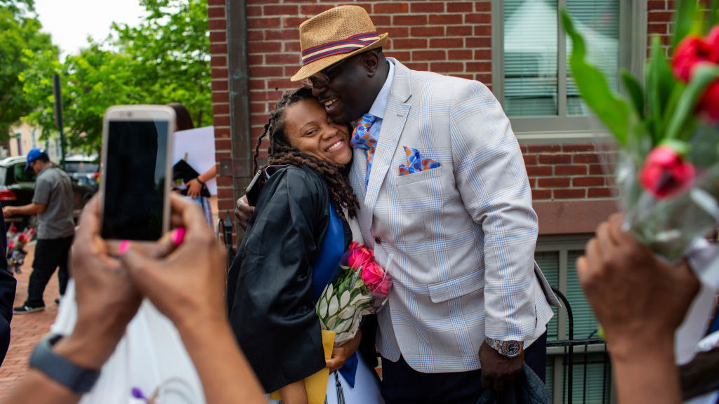 Rashema Melson gets a hug and has her photo taken with her cousin Anthony Young after the 2019 Georgetown University graduation ceremony.