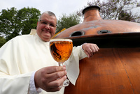 The Rev. Karel Stautemas poses with a Grimbergen beer in the courtyard of the Belgian Abbey of Grimbergen. Karel says the abbey's fathers will return to brewing after a break of two centuries.