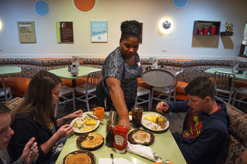Tanisha Cortez waits on a table at a restaurant in Ames, Iowa. When the previous restaurant she worked for closed, Cortez applied to others and had job offers right away. Jobs are plentiful in Ames, a small city of more than 65,000 residents tucked amid farm fields north of Des Moines. (Olivia Sun for NPR)