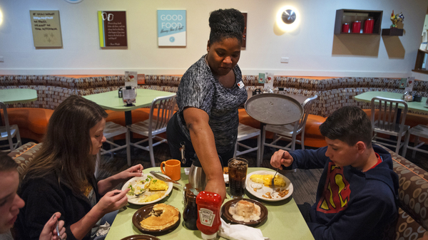 Tanisha Cortez waits on a table at a restaurant in Ames, Iowa. When the previous restaurant she worked for closed, Cortez applied to others and had job offers right away. Jobs are plentiful in Ames, a small city of more than 65,000 residents tucked amid farm fields north of Des Moines.