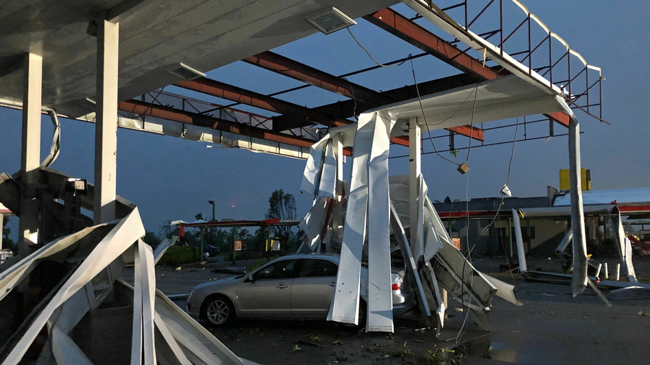 A car is trapped under the fallen metal roof of the Break Time gas station and convenience store in tornado-hit Jefferson City, Mo., on Thursday.